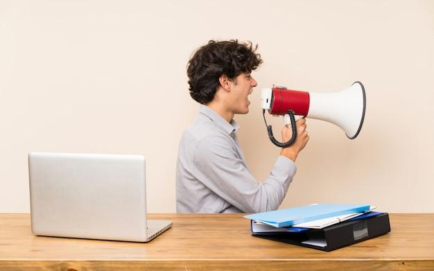 Młody studencki mężczyzna krzyczy przez megafonu z laptopem