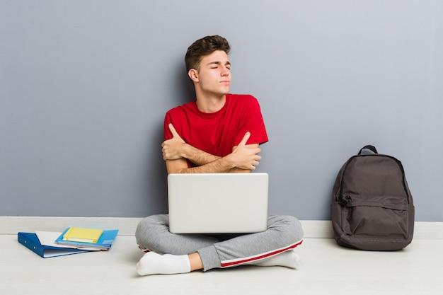 Młody studencki mężczyzna obsiadanie na jego domowej podłoga trzyma laptop