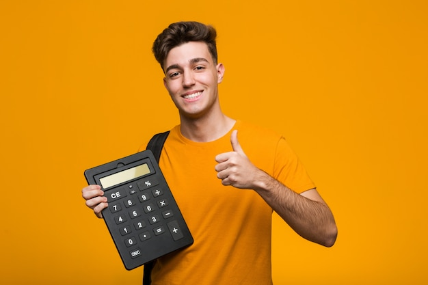 Młody studencki mężczyzna trzyma kalkulatora pokazuje zwycięstwo znaka i ono uśmiecha się szeroko.