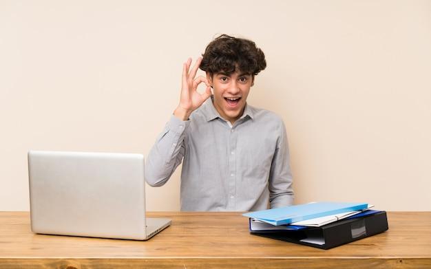 Młody studencki mężczyzna z laptopem zaskakującym i pokazuje ok znaka