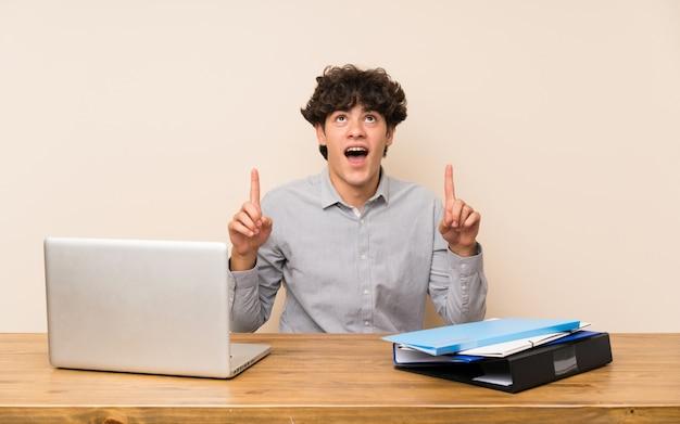 Młody studencki mężczyzna z laptopem zaskakującym i wskazuje up