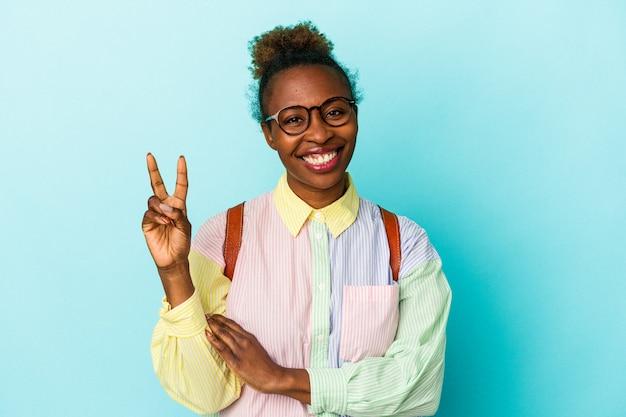 Młody student african american kobieta na białym tle wyświetlono numer dwa palcami.