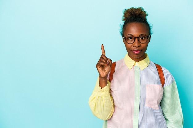 Młody student african american kobieta na białym tle wyświetlono numer jeden z palcem.