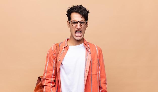 Młody student agresywnie krzyczący, wyglądający na bardzo złego, sfrustrowanego, oburzonego lub zirytowanego, krzyczący nie