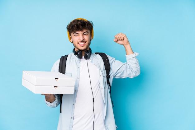 Młody student arabski mężczyzna trzyma pizze na białym tle podnosząc pięść po zwycięstwie, koncepcja zwycięzcy.