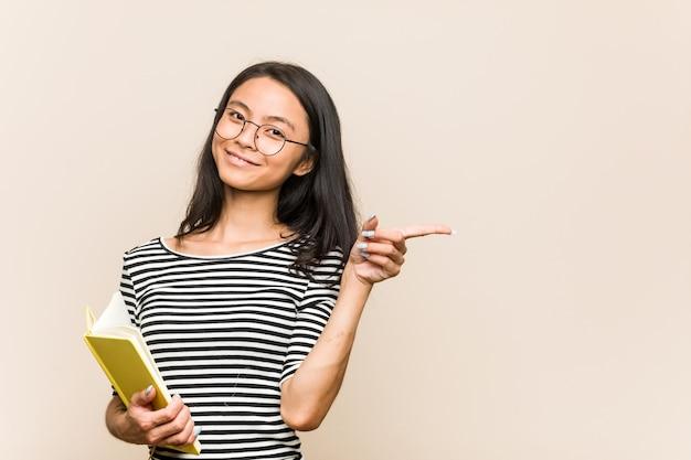 Młody student azjatyckich kobieta trzyma książkę, uśmiechając się i wskazując na bok, pokazując coś w pustym miejscu.