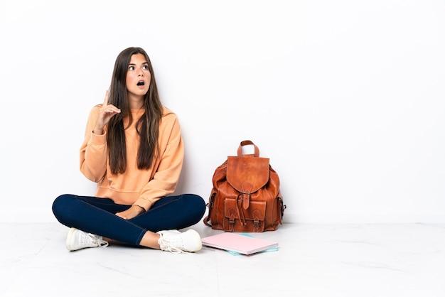 Młody student brazylijski kobieta siedzi na podłodze, myśląc pomysł, wskazując palcem w górę