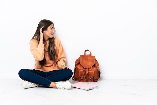 Młody student brazylijski kobieta siedzi na podłodze, słuchając czegoś, kładąc rękę na uchu