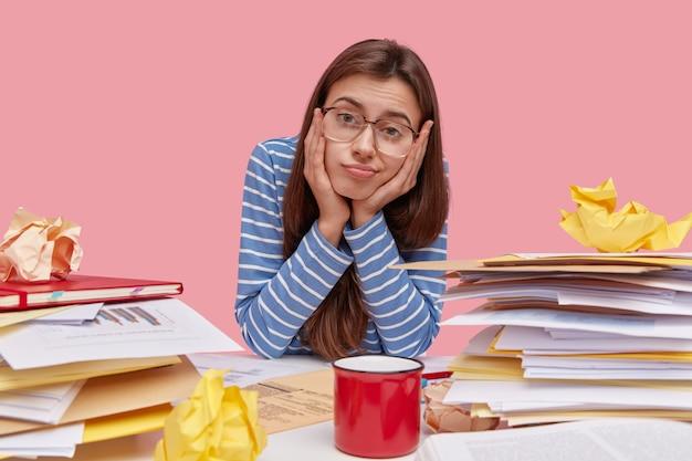 Młody student brunetka siedzi przy biurku z książkami