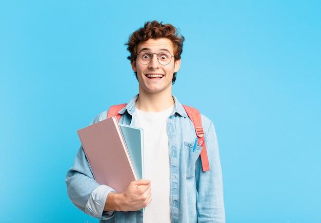 Młody student chłopca wyglądający na szczęśliwego i mile zaskoczonego, podekscytowany zafascynowanym i zszokowanym wyrazem twarzy