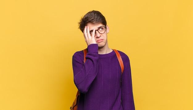 Młody student chłopiec czuje się znudzony, sfrustrowany i senny po męczącym, nudnym i żmudnym zadaniu trzymając twarz w dłoni