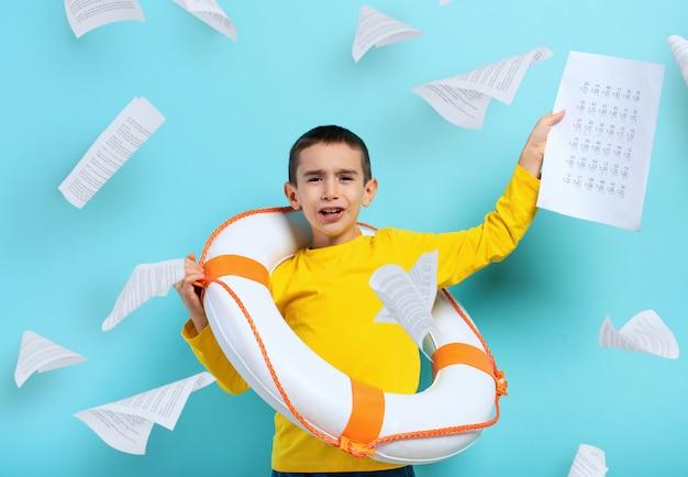 Młody student chłopiec tonie w morzu arkuszy ćwiczeń. niebieskie tło