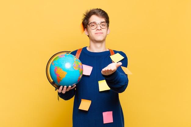Młody student chłopiec uśmiechający się radośnie z przyjaznym, pewnym siebie, pozytywnym wyglądem, oferujący i pokazujący przedmiot lub koncepcję
