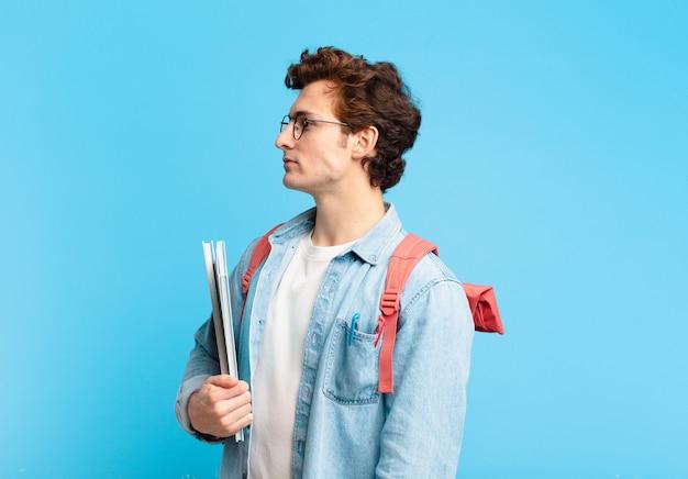 Młody student chłopiec w widoku profilu, który chce skopiować przestrzeń do przodu, myśląc, wyobrażając sobie lub marząc na jawie