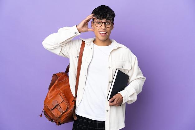 Młody student człowiek na pojedyncze fioletowe ściany z wyrazem zaskoczenia