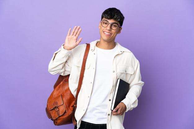 Młody student człowiek na pojedyncze fioletowe tło salutowanie ręką z happy wypowiedzi