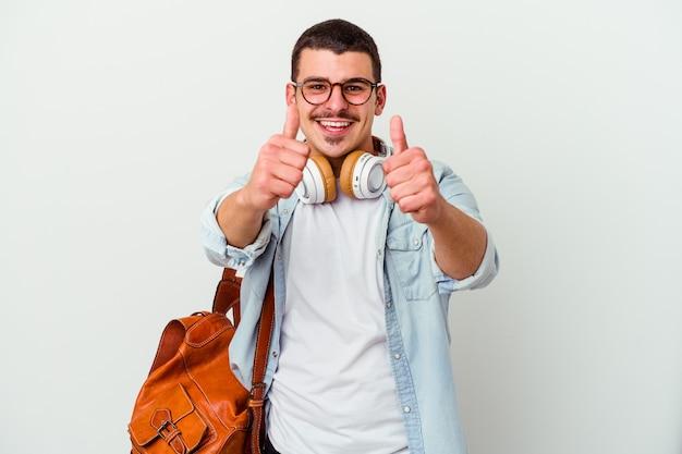 Młody student człowiek słuchanie muzyki na białym tle na białej ścianie z kciuki do góry, wiwaty o czymś
