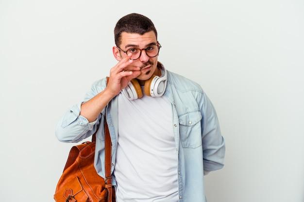 Młody student człowiek słuchanie muzyki na białym tle na białej ścianie z palcami na ustach, zachowując tajemnicę