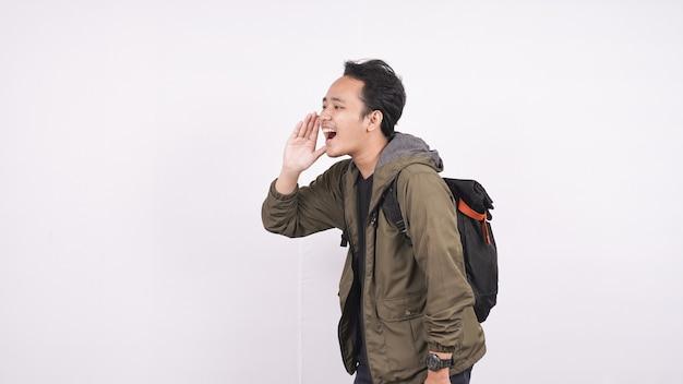 Młody student człowiek ubrany w torbę krzycząc i wrzeszcząc na białym tle na białym tle