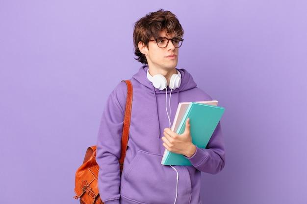 Młody student czuje się smutny, zdenerwowany lub zły i patrzy w bok