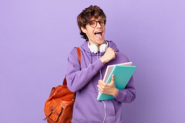 Młody student czuje się szczęśliwy i stoi przed wyzwaniem lub świętuje