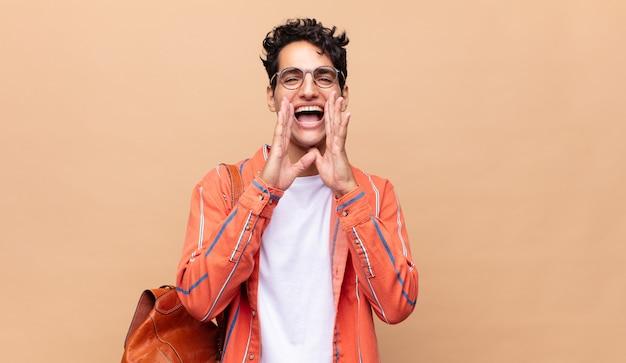 Młody student czuje się szczęśliwy, podekscytowany i pozytywnie nastawiony, wydając wielki okrzyk z rękami przy ustach, wołając