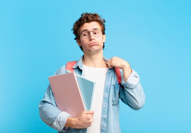 Młody student czuje się zestresowany, niespokojny, zmęczony i sfrustrowany, ciągnie za koszulkę, wygląda na sfrustrowanego problemem