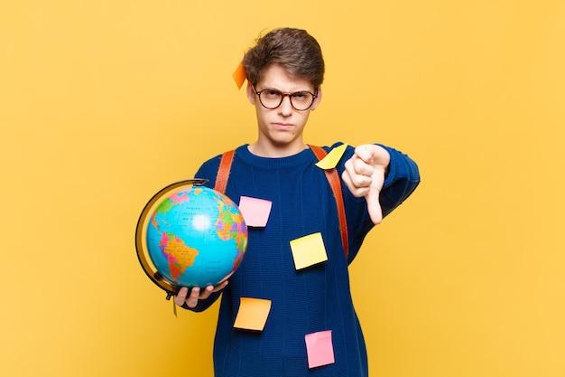 Młody student czuje się zły, zły, zirytowany, rozczarowany lub niezadowolony, pokazując kciuk w dół z poważnym spojrzeniem