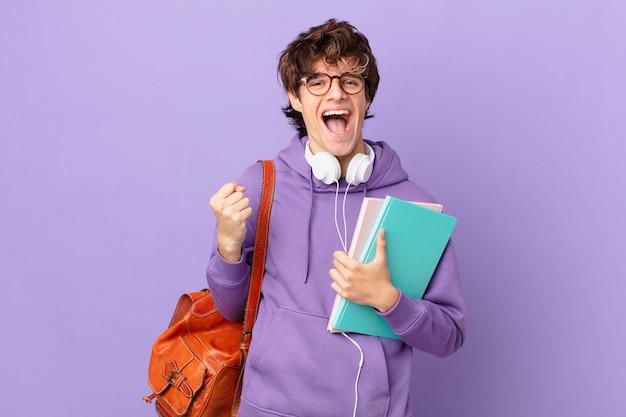 Młody student czuje się zszokowany, śmieje się i świętuje sukces