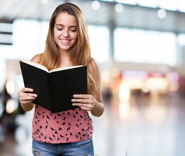 Młody student czytanie książki na białym tle