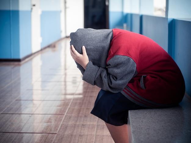 Młody student dziewczyna siedzi sam ze smutnym uczuciem w szkole
