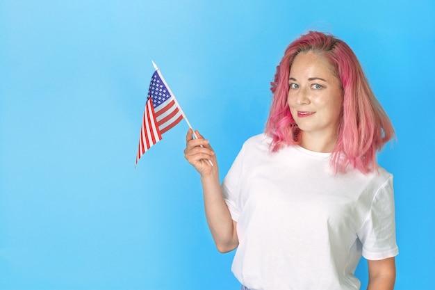 Młody student dziewczyna trzyma amerykańską małą flagę i uśmiecha się na niebieskim tle, szczęśliwa kobieta trzyma flagę usa. uczyć się angielskiego. studia za granicą, międzynarodowe kursy językowe.