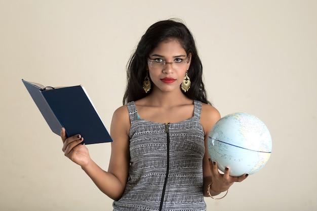 Młody student dziewczyna trzyma książkę z kulą ziemską na białej ścianie. edukacja w koncepcji college'u liceum