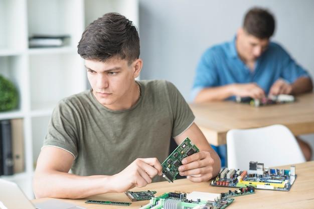 Młody student informatyki, który ćwiczy sprzęt komputerowy na stole warsztatowym