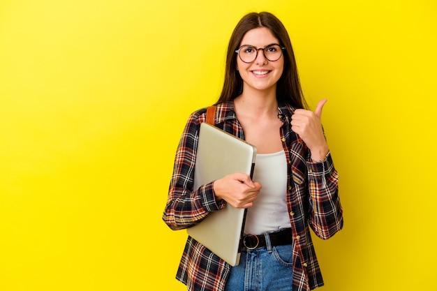 Młody student kaukaski kobieta trzyma laptop na białym tle na różowym tle uśmiechając się i podnosząc kciuk do góry