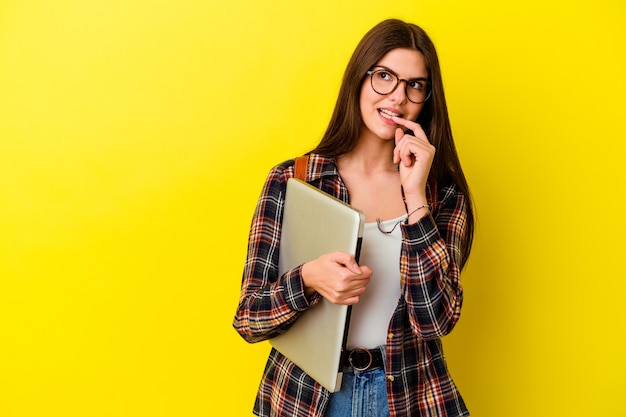 Młody student kaukaski kobieta trzyma laptopa na białym tle na różowej ścianie zrelaksowany myślenie o czymś patrząc na przestrzeń kopii.
