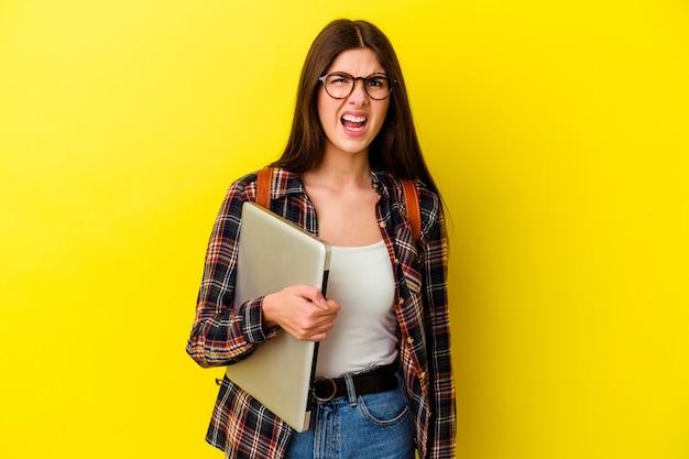 Młody student kaukaski kobieta trzyma laptopa na różowo krzyczy bardzo zły i agresywny.