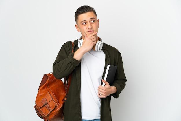 Młody student kaukaski mężczyzna na białym tle wątpliwości