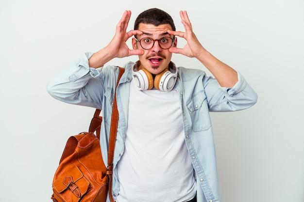 Młody student kaukaski mężczyzna słucha muzyki na białym tle na białej ścianie, trzymając oczy otwarte, aby znaleźć okazję do sukcesu.