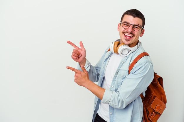 Młody student kaukaski mężczyzna słucha muzyki na białym tle, wskazując palcami wskazującymi na przestrzeń kopii, wyrażając podekscytowanie i pożądanie.