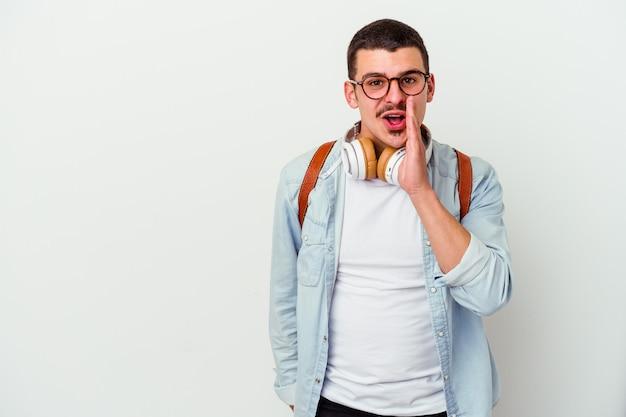 Młody student kaukaski mężczyzna, słuchając muzyki na białym tle, mówi tajną wiadomość o gorącym hamowaniu i patrzy na bok