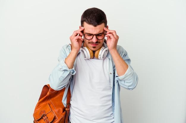 Młody student kaukaski mężczyzna słuchania muzyki na białym tle dotykając świątyń i mając ból głowy.