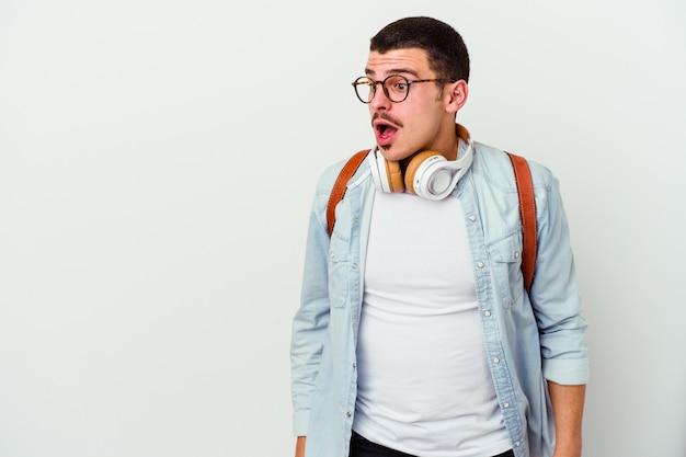 Młody student kaukaski mężczyzna słuchania muzyki na białym tle jest zszokowany z powodu czegoś, co widziała.