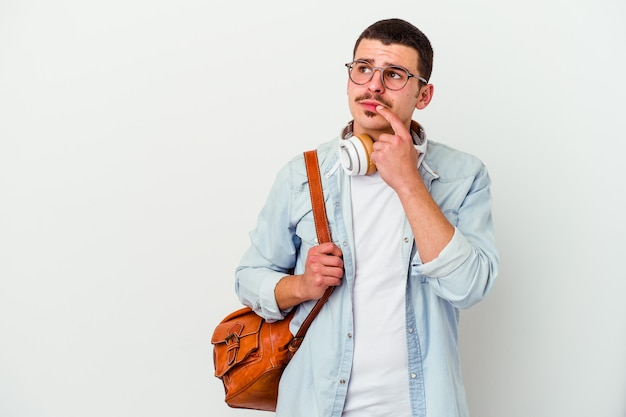 Młody student kaukaski mężczyzna słuchanie muzyki na białym, patrząc w bok z wyrazem wątpliwości i sceptycyzmu.