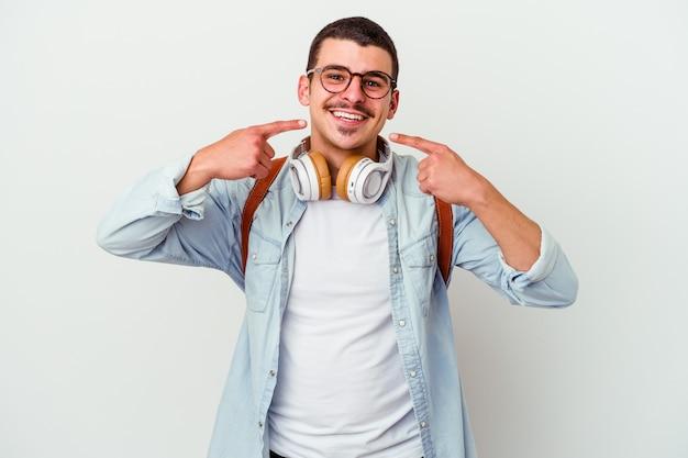 Młody student kaukaski mężczyzna, słuchanie muzyki na białym tle na białej ścianie uśmiecha się, wskazując palcami na usta.