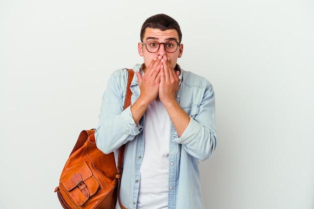 Młody student kaukaski mężczyzna słuchanie muzyki na białym tle zszokowany obejmując usta rękami.
