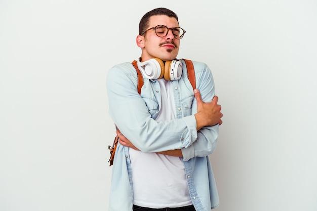 Młody student kaukaski mężczyzna słuchanie muzyki na białym tle