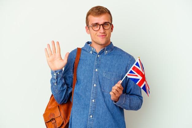 Młody student kaukaski mężczyzna studiuje angielski na białym tle na białej ścianie uśmiechnięty wesoły pokazując numer pięć palcami.