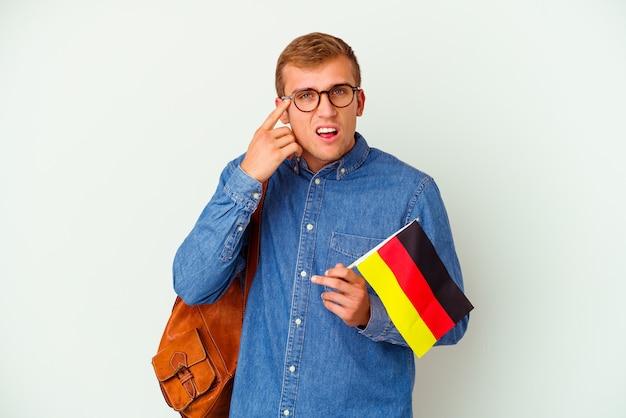 Młody student kaukaski mężczyzna studiuje niemiecki na białym tle na białej ścianie pokazując gest rozczarowania palcem wskazującym.