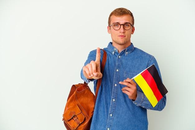 Młody student kaukaski mężczyzna studiuje niemiecki na białym tle na białym tle pokazując numer jeden z palcem.
